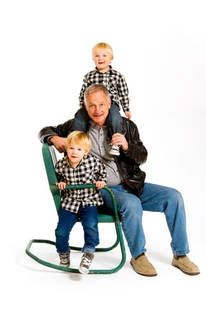 A grandfather with two boys in the studio on an isolated white background with a green rocking chair. Stock Photo - 17514953