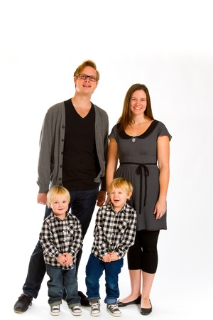 An attractive couple and their two sons against an isolated white background in the studio for a family portrait. Stock Photo - 17514892