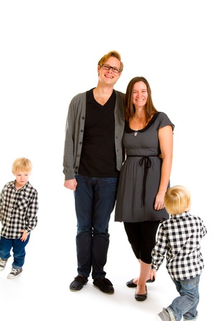 A couple stands there as their children run circles around them in the studio against an isolated white background. Stock Photo - 17512007