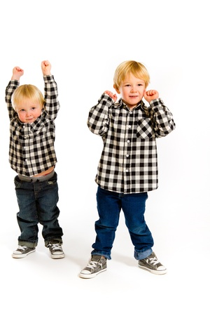 A boy and his sibling brother pose for this portrait in a studio against an isolated white background. Stock Photo - 17585016