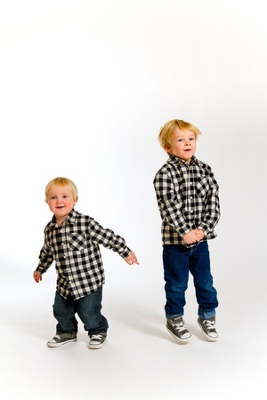 A boy and his sibling brother pose for this portrait in a studio against an isolated white background. Stock Photo - 17514915