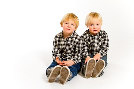 A boy and his sibling brother pose for this portrait in a studio against an isolated white background. Stock Photo - 17514945