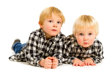 A boy and his sibling brother pose for this portrait in a studio against an isolated white background. Stock Photo - 17515210