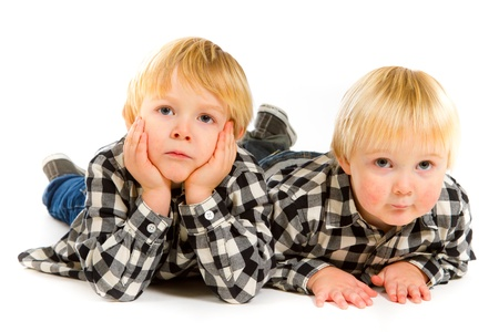 A boy and his sibling brother pose for this portrait in a studio against an isolated white background. Stock Photo - 17515255