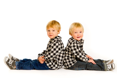 A boy and his sibling brother pose for this portrait in a studio against an isolated white background.