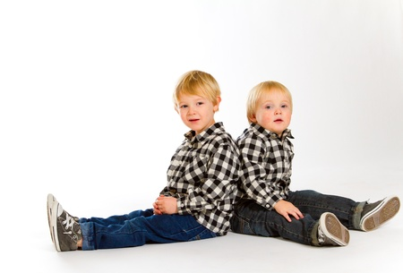 A boy and his sibling brother pose for this portrait in a studio against an isolated white background. Stock Photo - 17514943