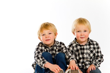 A boy and his sibling brother pose for this portrait in a studio against an isolated white background. Stock Photo - 17514974