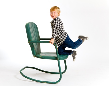 A boy in a plaid shirt has a fun time playing on this green rocking chair against an isolated white background in the studio. Stock Photo - 17512011