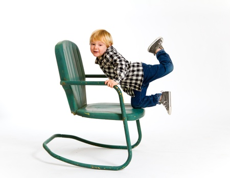 A boy in a plaid shirt has a fun time playing on this green rocking chair against an isolated white background in the studio. Stock Photo - 17512010