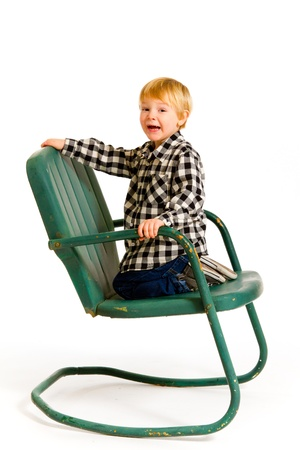 A boy in a plaid shirt has a fun time playing on this green rocking chair against an isolated white background in the studio. Stock Photo - 17514911