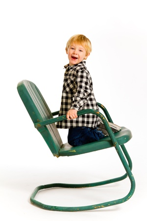A boy in a plaid shirt has a fun time playing on this green rocking chair against an isolated white background in the studio. Stock Photo - 17514897