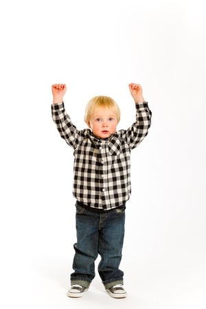 A young boy in a plaid shirt poses for this portrait in the studio against an isolated white background Stock Photo - 17544155