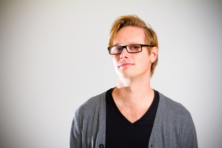 This contemporary style portrait of a man wearing a black shirt and a grey cardigan sweater while wearing glasses in the studio  Stock Photo - 17544170