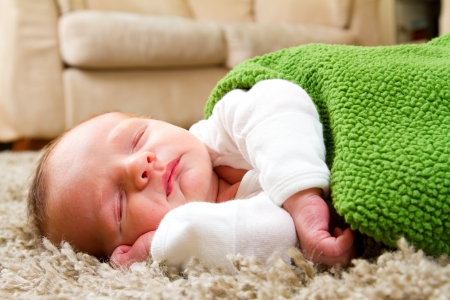 wrapped up: A newborn baby boy sleeps on a comfy rug in the living room while wrapped up in a warm green blanket  Stock Photo