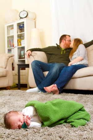 A newborn baby boy lays on a rug with his parents in the background indoors at their house  photo