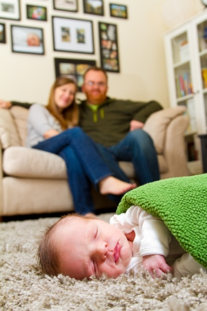 A newborn baby boy lays on a rug with his parents in the background indoors at their house 版權商用圖片 - 17544175