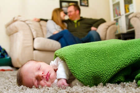 A newborn baby boy lays on a rug with his parents in the background indoors at their house  版權商用圖片