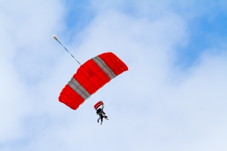 A person skydiving with their parachute open floats towards the ground on the north shore of Oahu. There are clouds in the blue sky with vibrant colors as the skydiver goes in for a landing.