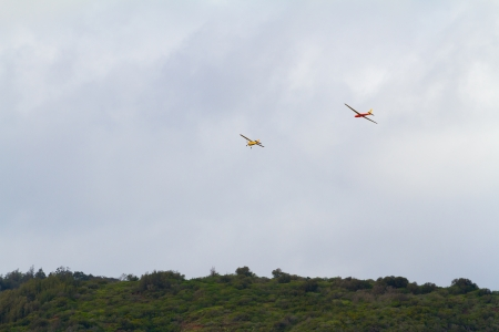 towed: A glider is being towed by another airplane for a takeoff above the tropical mountains on the north shore of Oahu. This unique aircraft glides through the air with no engine.