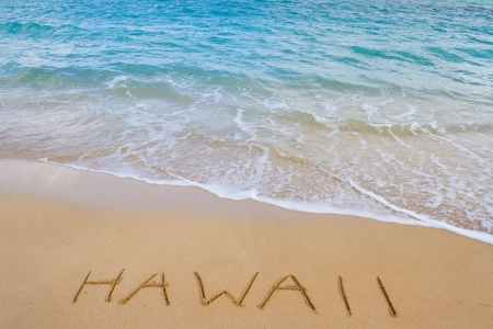 come in: The word Hawaii is written in the sand of this beach as waves come in to wash it away. This is a vacation image showing the tropical location with sand and water of the Ocean. Stock Photo