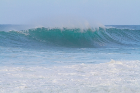 banzai pipeline: These huge waves with hollow barrels break off the north shore of Oahu in Hawaii during a big storm. These dangerous waves have major rip currents and a lot of power from the ocean but surfers are still lining up to surf. Stock Photo