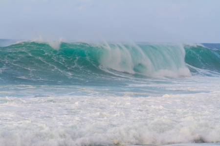 major ocean: These huge waves with hollow barrels break off the north shore of Oahu in Hawaii during a big storm. These dangerous waves have major rip currents and a lot of power from the ocean but surfers are still lining up to surf. Stock Photo