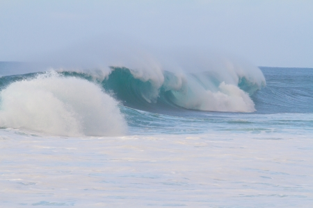 swell: These huge waves with hollow barrels break off the north shore of Oahu in Hawaii during a big storm. These dangerous waves have major rip currents and a lot of power from the ocean but surfers are still lining up to surf. Stock Photo