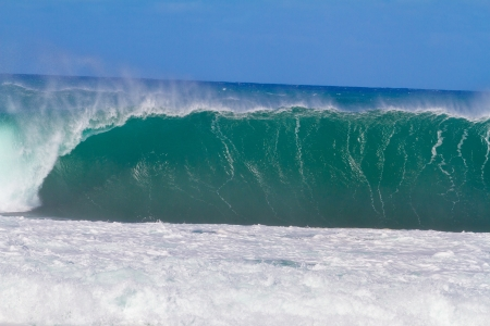 banzai pipeline: Large waves break off the north shore of oahu hawaii during a great time for surfers surfing. These waves have hollow barrells and are located at pipeline by sunset beach.