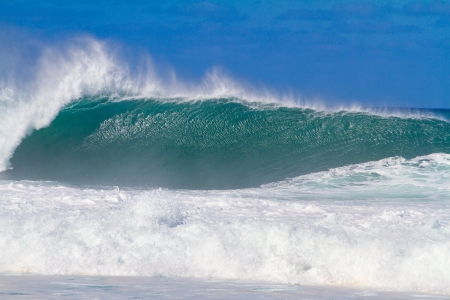 Large waves break off the north shore of oahu hawaii during a great time for surfers surfing. These waves have hollow barrells and are located at pipeline by sunset beach.