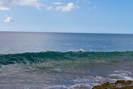 banzai pipeline: These almost completely clear waves are swelling and breaking onto some rocks on Oahu Hawaii. These waves are interesting and different than most.