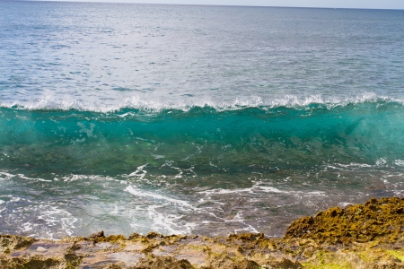 These perfectly clear waves form and break on some rocks in a dangerous spot on the west shore of Oahu in Hawaii  You can see right through the waves and the vibrant color of the ocean really shows Stock Photo - 18229698
