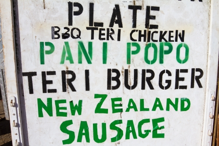 pani: A food truck in Oahu Hawaii has a painted stenciled sign showing the menu for plate lunches
