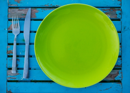 An empty green plate on a weathered blue table along with a fork and knife sits ready to be served a meal for eating