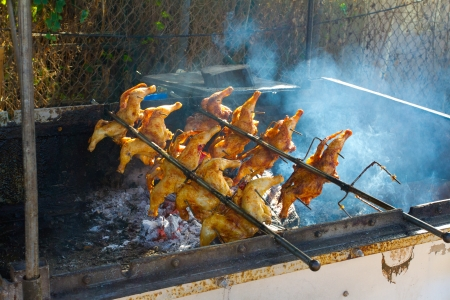 Barbeque chicken is being cooked over a wood fire with a rotisserie in Hawaii for lunch plates.