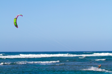 north shore: A man kite surfing in the waves along the north shore of Oahu. The kite is high above in the sky with plenty of wind to propel the man through the water on his surf board. Stock Photo