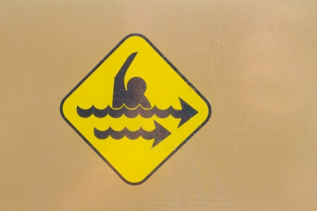 danger: A warning sign icon shows the danger of a strong rip current. This yellow hazard sign is universal.
