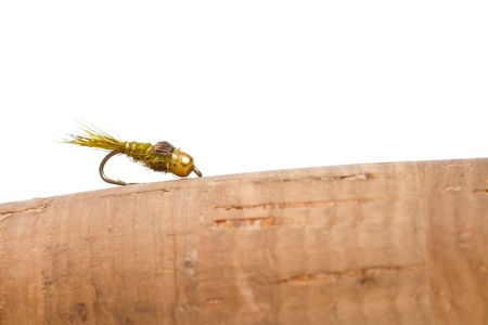 Isolated in a studio with a white background a hares ear nymph in natural colors is photographed closeup against the cork handle of a fly fishing rod. Stock Photo - 18229019
