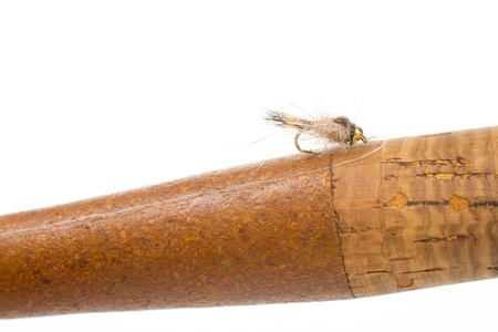 Isolated in a studio with a white background a hares ear nymph in natural colors is photographed closeup against the cork handle of a fly fishing rod. photo