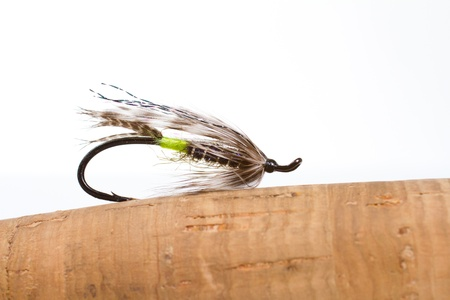 This green butted silver hilton steelhead fly fishing streamer is isolated against a white background in the studio along with the cork handle of the fly fishing rod. photo