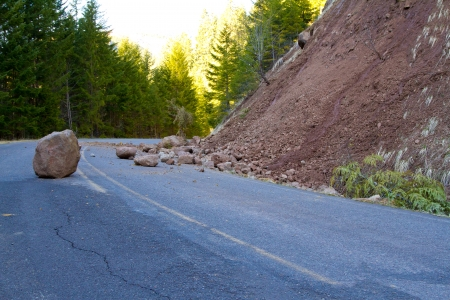 landslide: This national forest road is blocked by a land slide of rock and debris to where it is a hazard for drivers in cars. Stock Photo