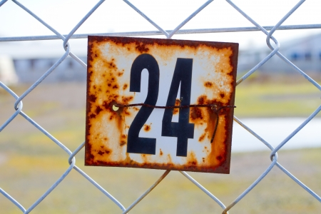 old sign: A series of rusted old signs or tags are attached to this chain link fence with orange and white rust and the numbers clearly visible