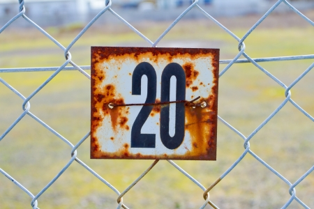 twenty two: A series of rusted old signs or tags are attached to this chain link fence with orange and white rust and the numbers clearly visible