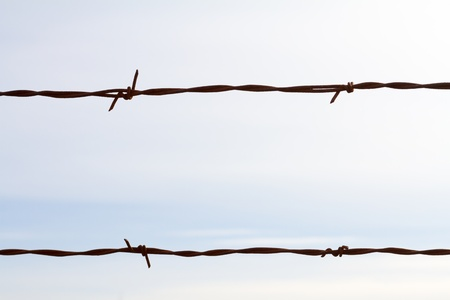 This color image shows nothing but a piece of barbed wire against a cloudy sky to create a very simple abstract background with the fencing Stock Photo - 18722953