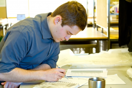 architect drawing: An architect studies in his college work building while drawing plans and preparing work for a class. Stock Photo