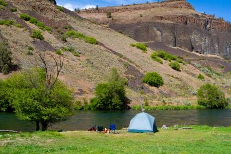 Een rustieke tent camping aan de rivier de Deschutes in Oregon toont een tent opzet naast een boot en de rivier. Dit is vormen een float kamperen.