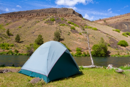 campsite: A rustic tent campsite on the Deschutes River in Oregon shows a tent setup next to a boat and the river. This is form a float camping trip.