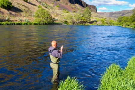 An experienced fly fisherman wades in the water while fly fishing the Deschutes River in Oregon. Stock Photo - 19983551