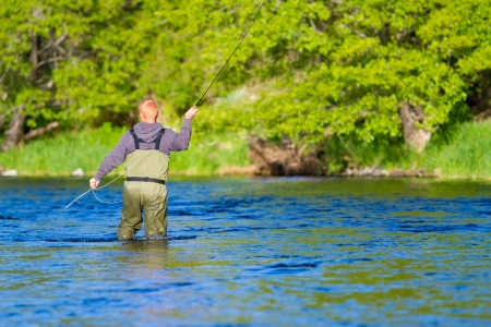 An experienced fly fisherman wades in the water while fly fishing the Deschutes River in Oregon. Stock Photo - 19983542