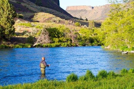 An experienced fly fisherman wades in the water while fly fishing the Deschutes River in Oregon.
