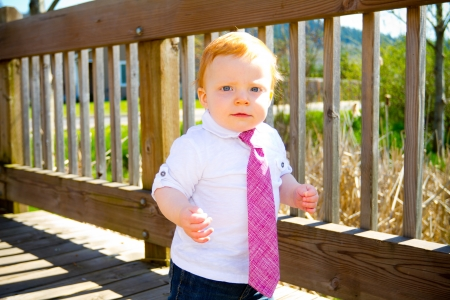 A one year old baby boy walks across a bridge wearing nice clothes and a necktie. Stock Photo